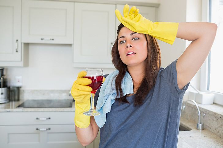 Woman standing holding a glass of wine after cleaning the house